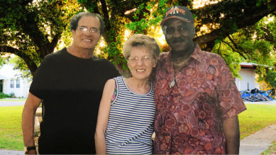 three people smiling in front of the camera